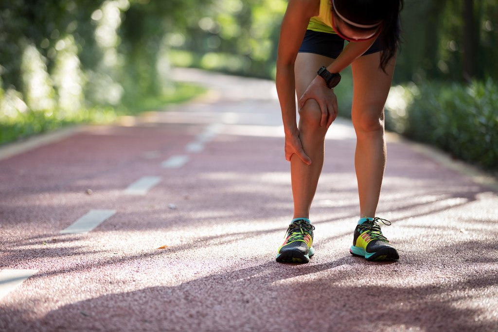 Female runner suffering with pain on sports running knee injuryFemale runner suffering with pain on sports running knee injury